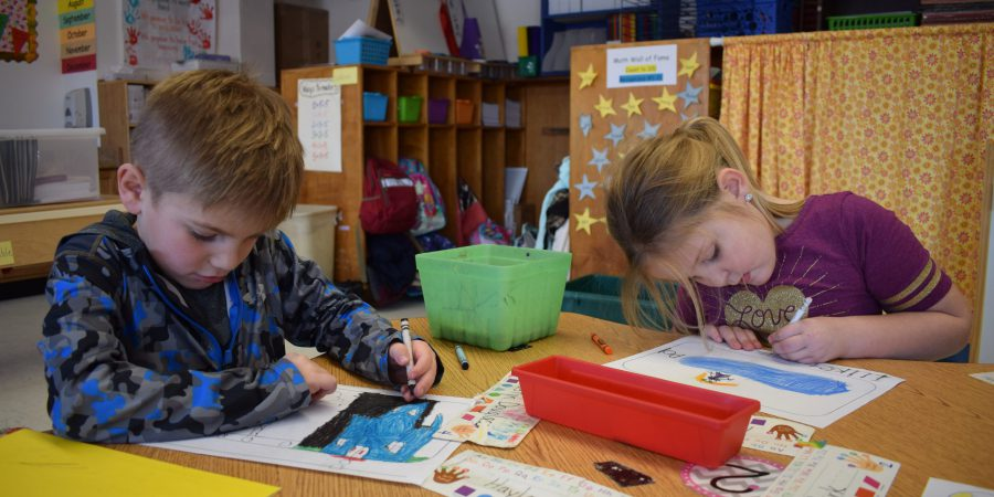 Two students are seen writing at a table